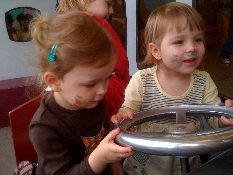 Kaia & Evelyn driving the bus at the Kid's Museum