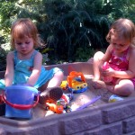 Happiness is two kids in a sandbox in the backyard