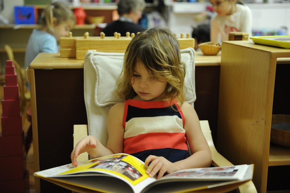 My girl enjoying a book at her Montessori preschool